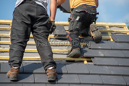 two carpenters working on roof