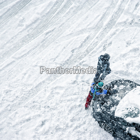 children play in snow around cars