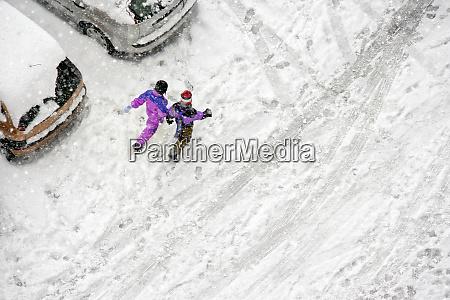 children play in snow around cars