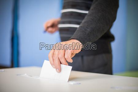 person voting casting a ballot