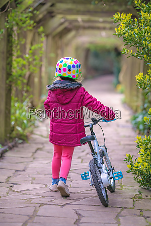 young little girl pushing her bicycle
