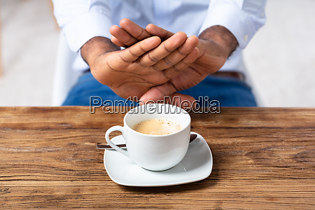 man refusing cup of coffee