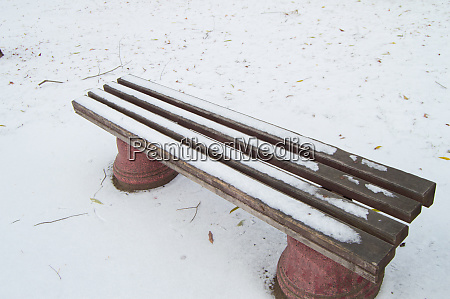 wooden bench in the winter city