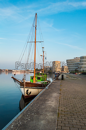 sailing ship and modern buildings in