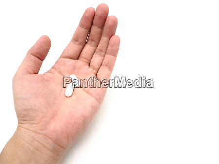 hand holding a white pills isolated