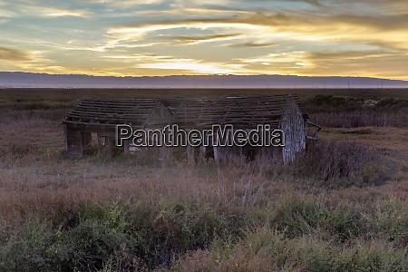 sunset over abandoned house at drawbridge