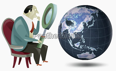 businessman looking at globe with magnifying