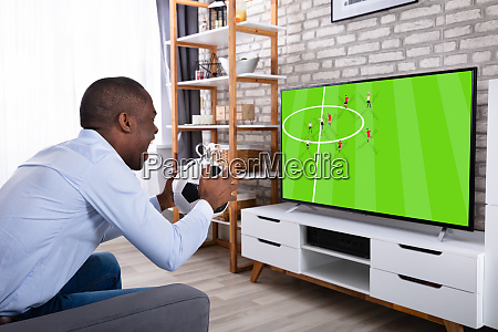 african man holding ball watching television