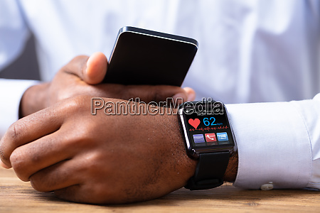 man holding mobile phone with smartwatch