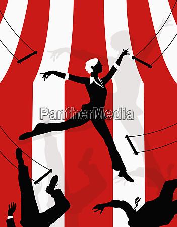 businesswoman swinging on trapeze