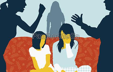 children on sofa between couple arguing
