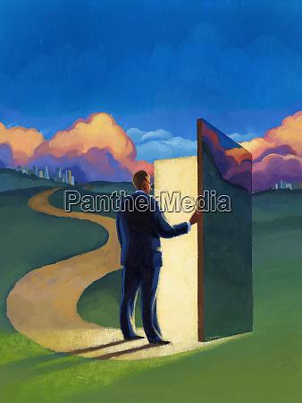 businessman in field opening door in