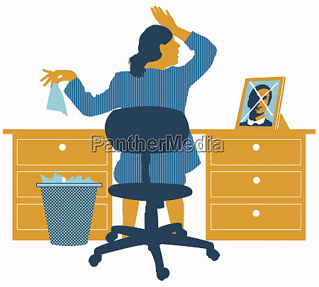upset businesswoman at desk with photo
