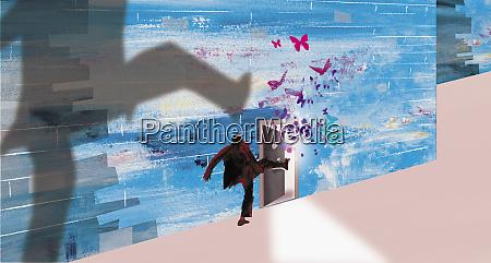 businessman kicking open door with butterflies
