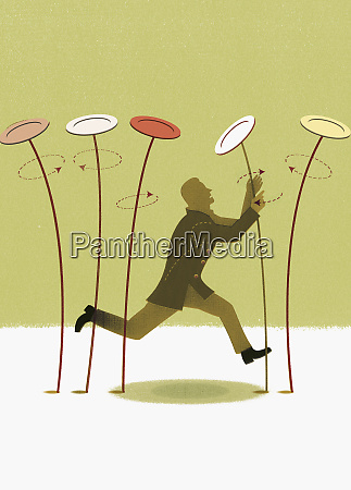 man spinning plates on stick