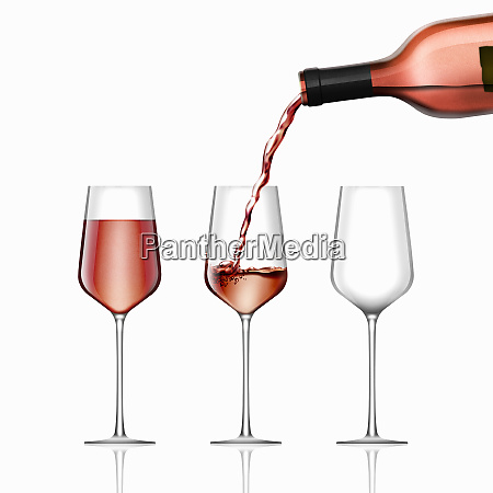 rose wine being poured into three