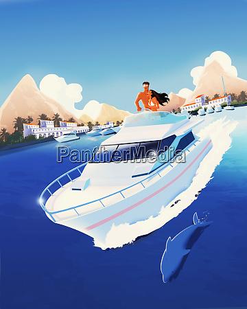 dolphin swimming alongside couple on yacht