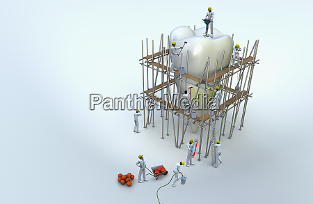 workmen on scaffolding repairing large tooth