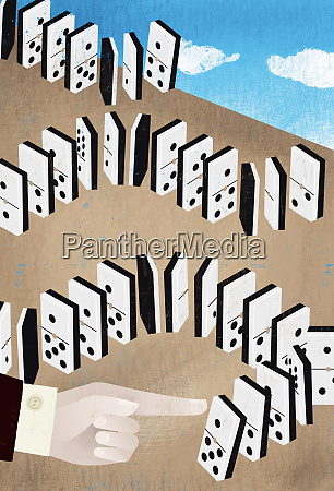 hand of businessman pushing domino with