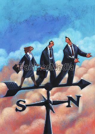 business people standing on weather vane
