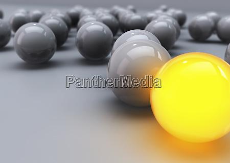 glowing yellow ball among grey balls