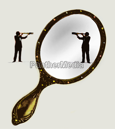 reflection of businessman with telescope in