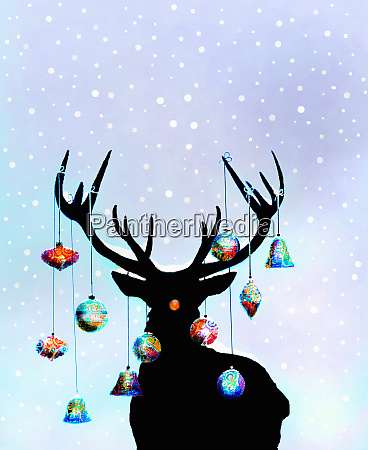 christmas ornaments hanging from antlers of