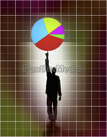 businessman balancing pie chart on pointing