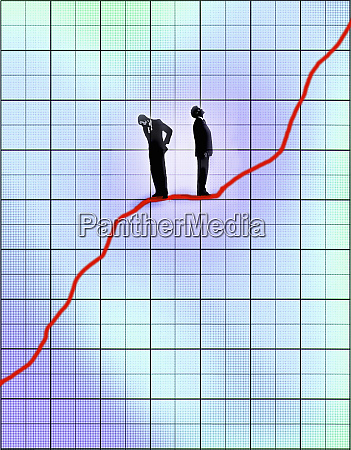 contrasting businessmen standing on line graph