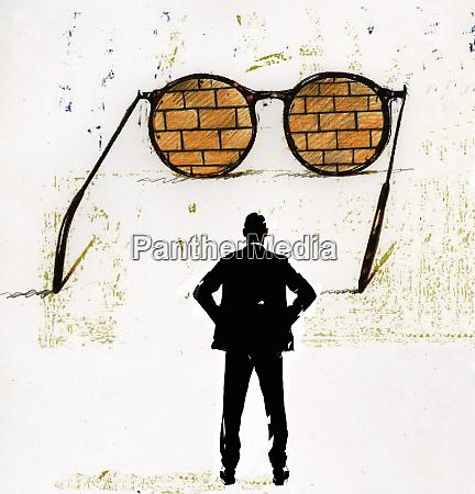 businessman looking at brick wall through