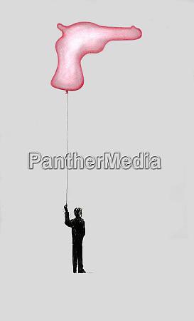 boy holding string of gun balloon