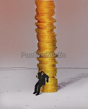 businessman protecting large pile of money