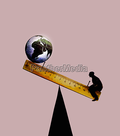 globe balancing on ruler seesaw with
