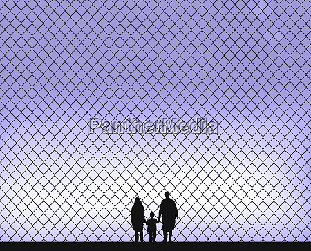 family holding hands behind wire fence
