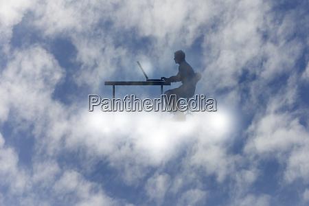 man using laptop at desk cloud