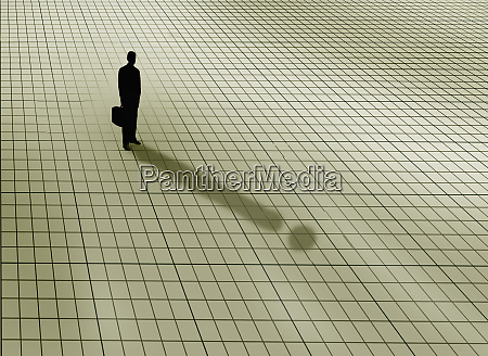 businessman standing on graph paper grid
