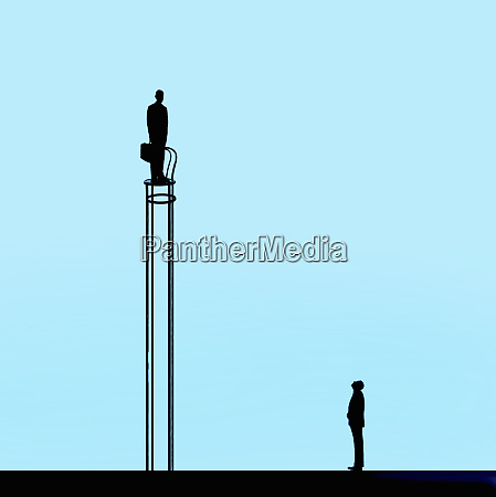 man looking up at businessman standing