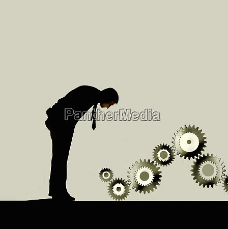 businessman examining connected cogs
