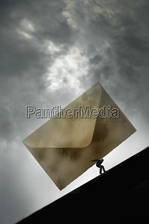man struggling uphill with large envelope