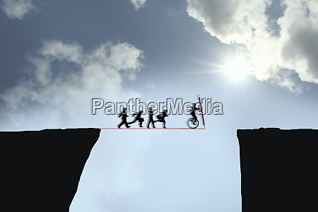 business people following businessman bridging the