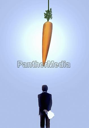 large carrot dangling above businessman