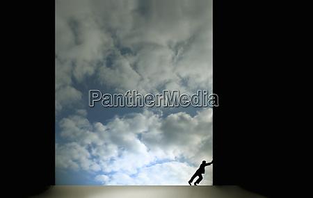 man pushing large dark sliding door