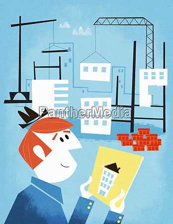businessman holding picture of house at