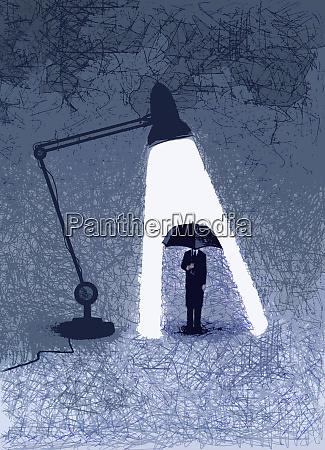 businessman hiding from light under umbrella