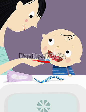 mother helping son brush teeth