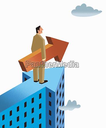 businessman on top of arrow skyscraper