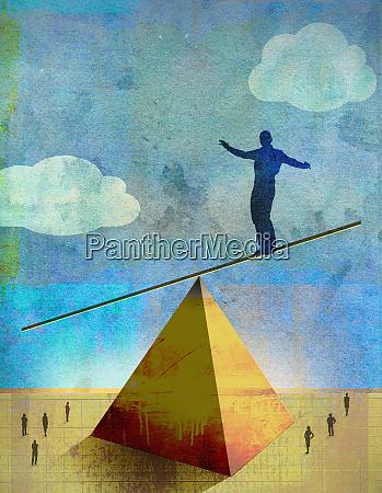 businessman precariously balancing on top of