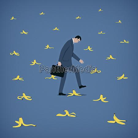 businessman avoiding lots of banana skins