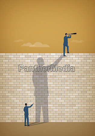 businessman seeing over wall supported by