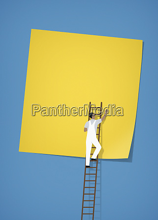 workman pasting large blank sticky note